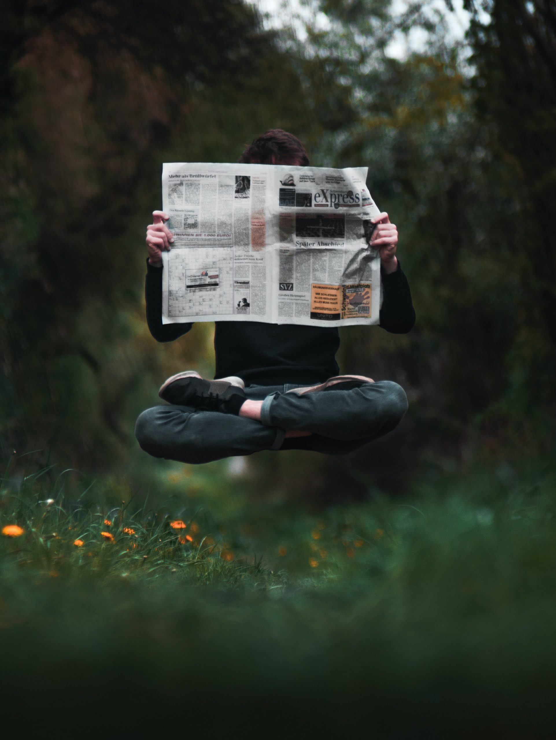 person holding a news paper during daytime